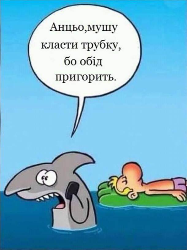 Смішний малюнок про акулу. На морі на надувному матрасі лежить чоловік і засмагає. Біля нього акула розмовляє по телефону: - Анцьо, мушу класти трубку, бо обід пригорить