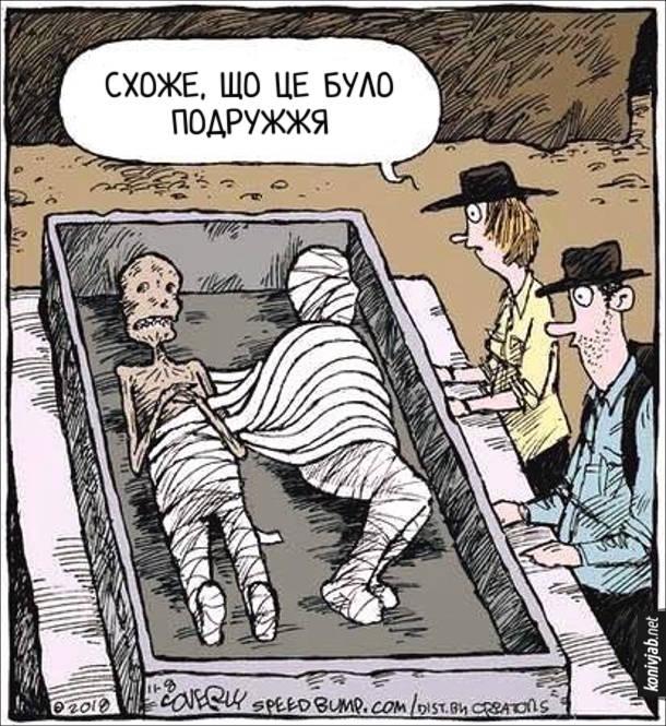 Смішний малюнок про мумію. Археологи відкрили гробницю з двома муміями. В одної мумії частково розгорнуті бинти і намотані на іншу мумію. Археолог: - Схоже, що це було подружжя (ніби дружина забрала бинти, неначе ковдру під час спання)