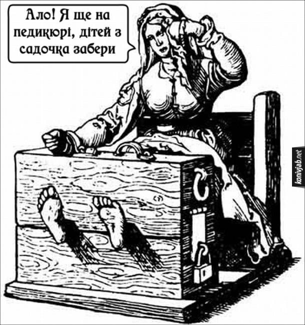Мем Середньовічні катування. Малюнок, де жінка на знарядді катування, в неї ноги забиті в колодки. Жінка ніби говорить по телефону: - Ало! Я ще на педикюрі, дітей з садочка забери