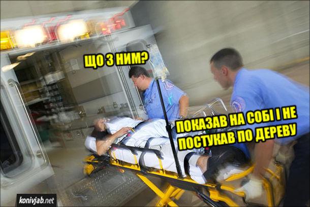 Мем про забобони. Санітари везуть хворого на ношав до машини швидкої допомоги. - Що з ним? - Показав на собі і не постукав по дереву