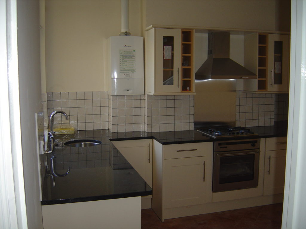 Kitchen with black granite worktops and brushed stainless splashback