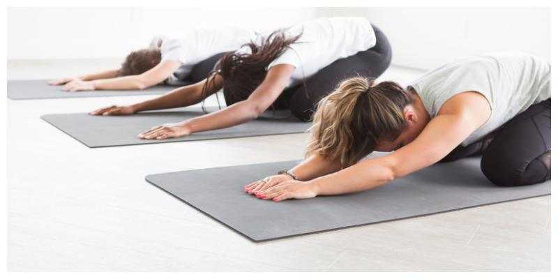 Three women doing yoga in relaxed pose, to relieve menopausal fatigue naturally.