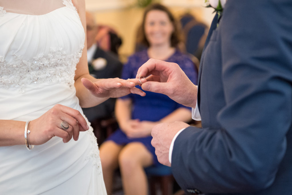 groom places ring on finger