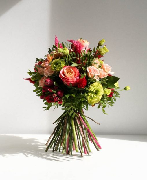 Bright peach and pink rose bouquet with green lisianthus and shocking pink celosia