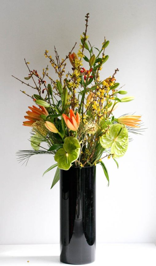 Contract and Office flowers, orange tulips with blossom in a black vase, created by north London florist...Garland
