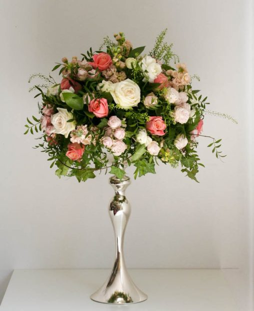 Peach tone tall wedding centrepiece, created by Garland London florist
