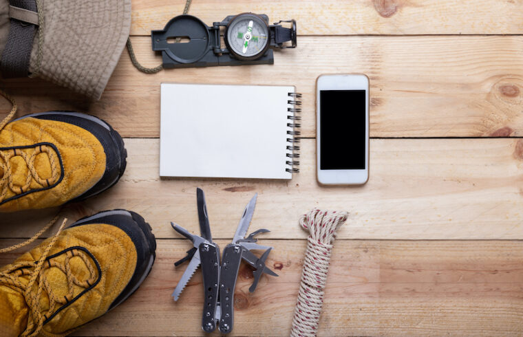 Outdoor travel equipment planning for a mountain trekking camping trip on wooden background. Top view