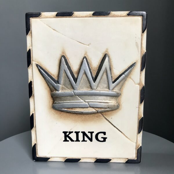 small silver crown with the word king underneath on a cram coloured block