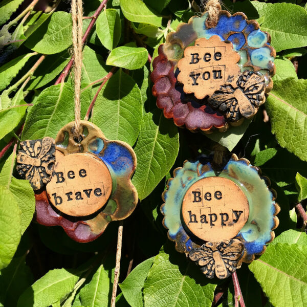 ceramic hangers with the words brave, you and happy