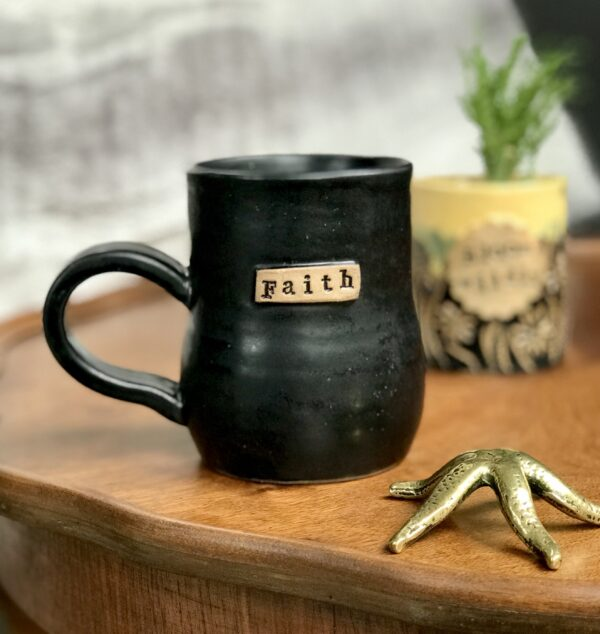 This Handmade Denby Pottery Mug is a beautiful shade of black with the embossed phrase saying 'faith'