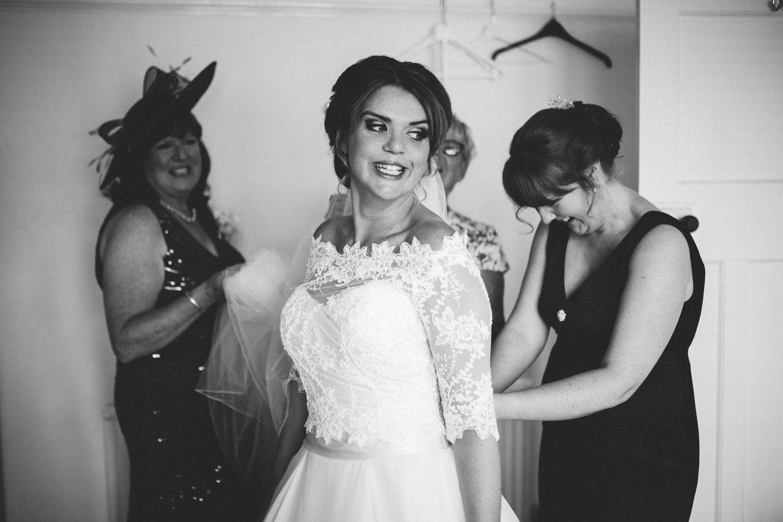 bride doing up dress