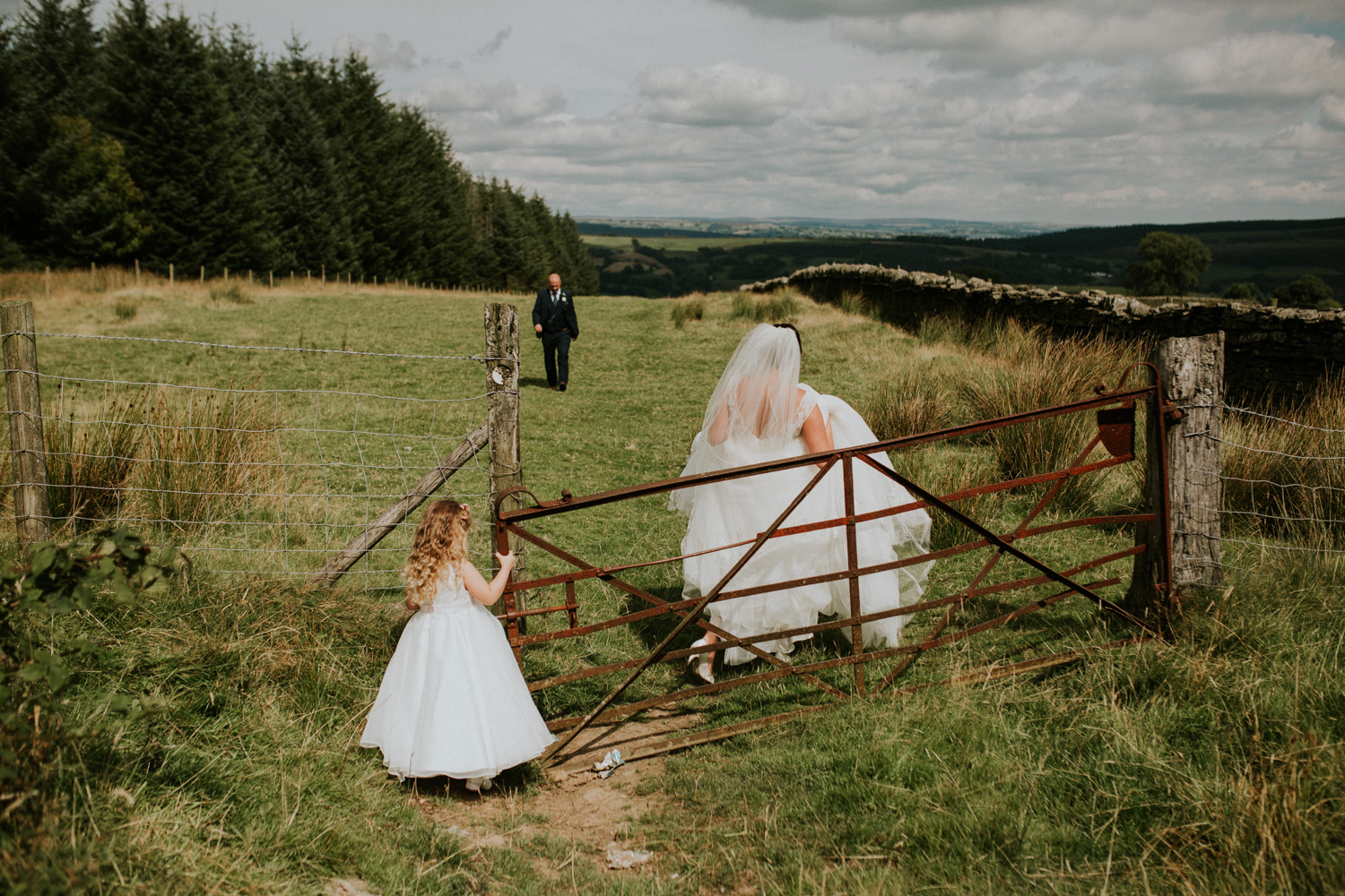 bride, groom and daughter in a field
