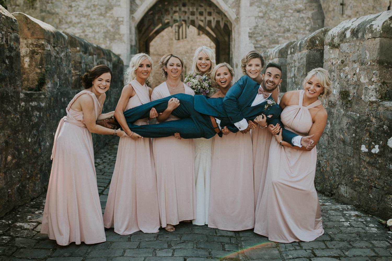 bridesmaids lifting the groom
