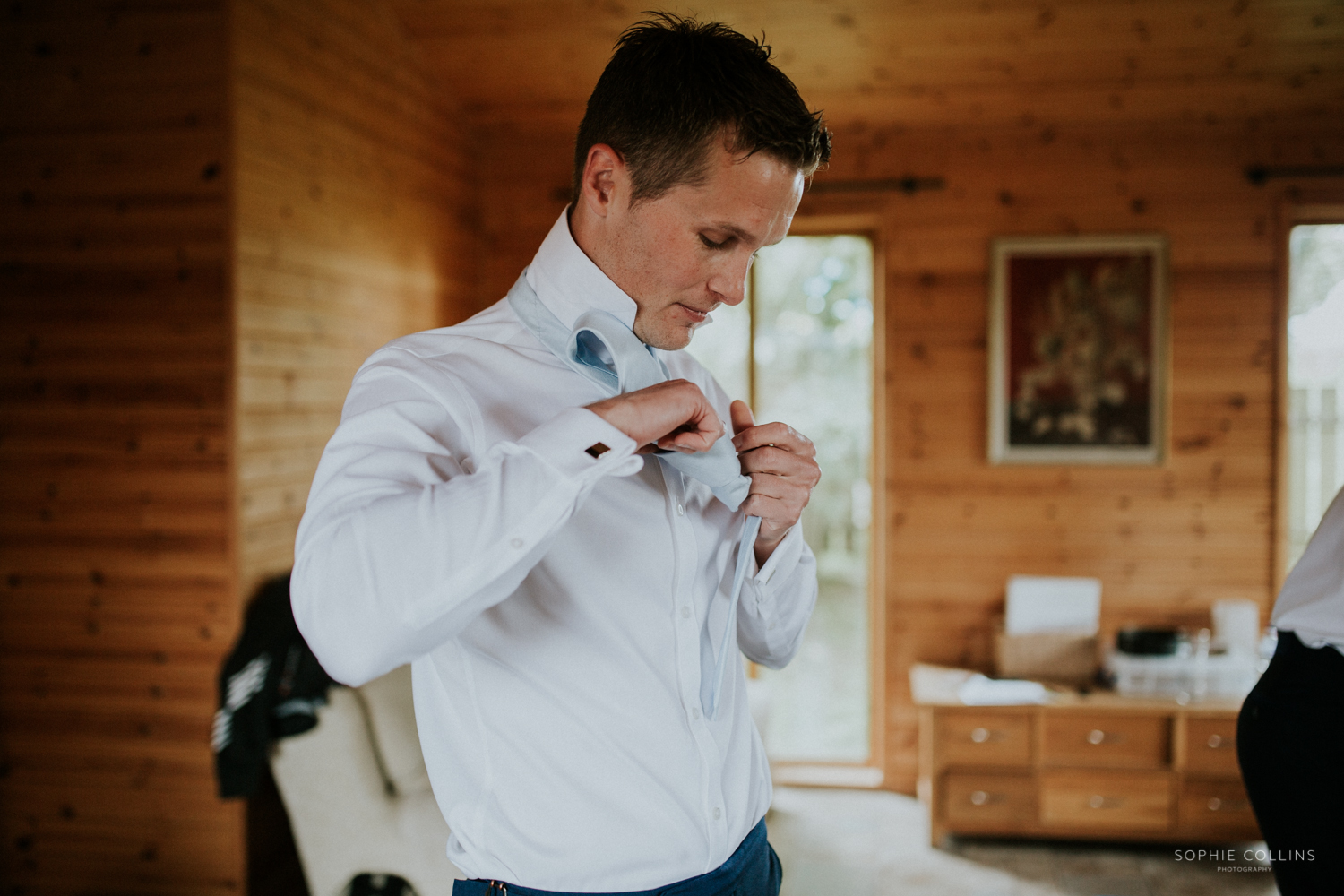 groom doing up his shirt