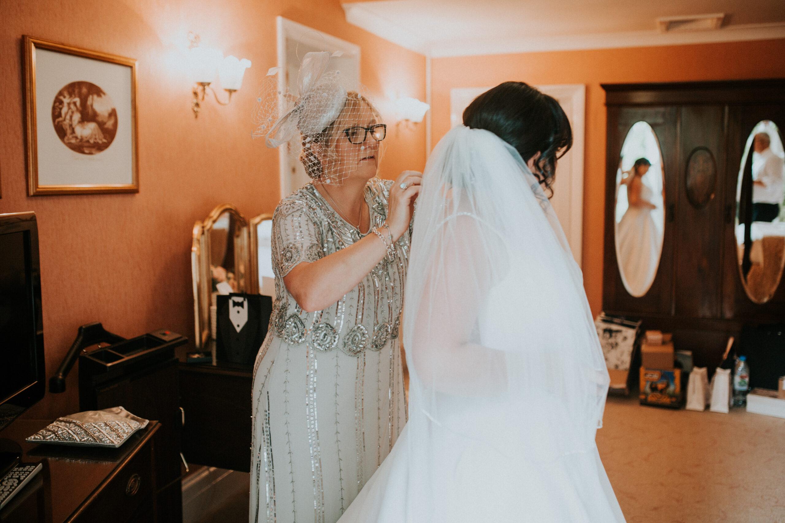 mother doing brides dress