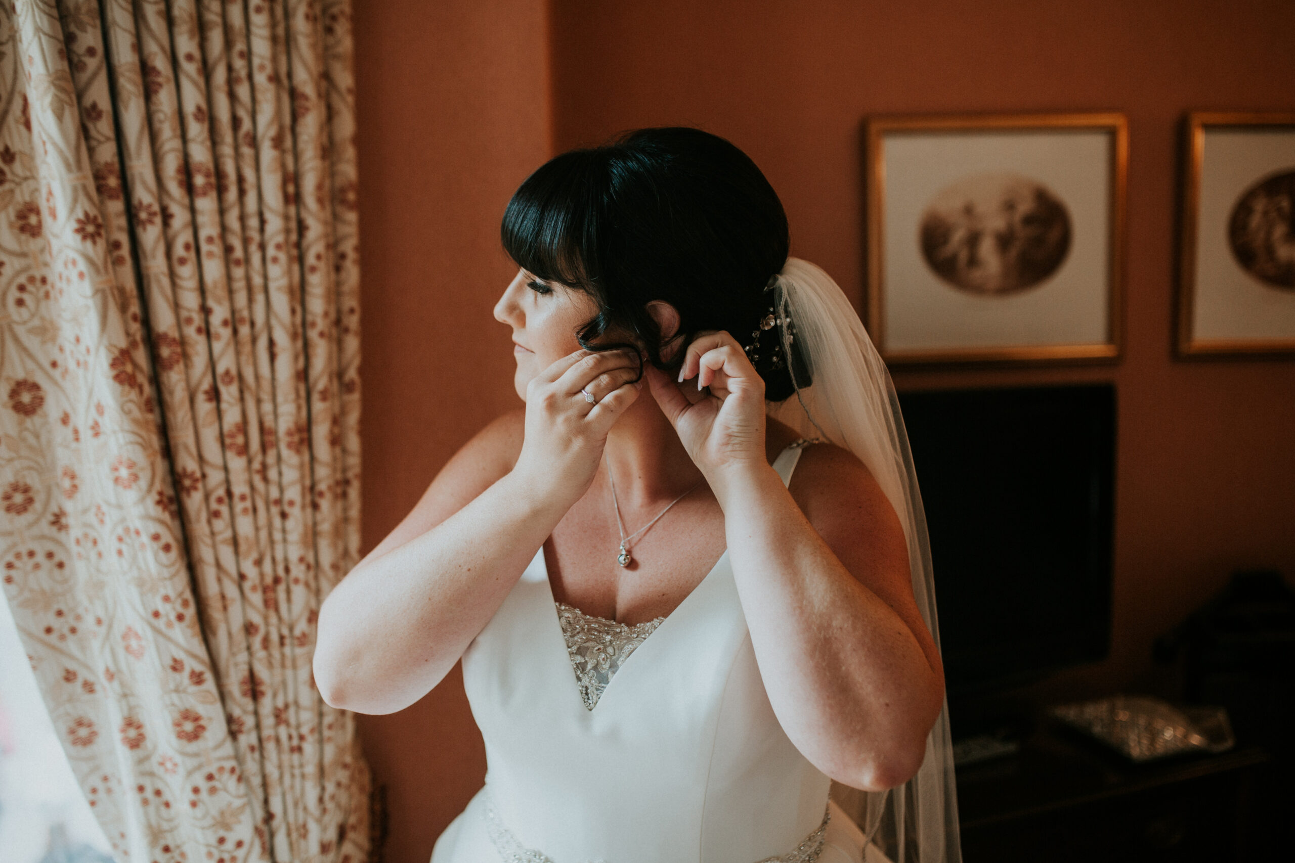 bride putting her earrings in