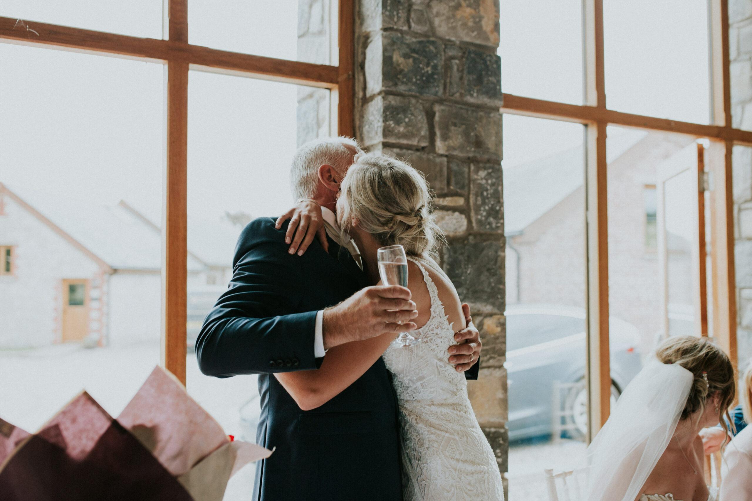 bride and dad hug
