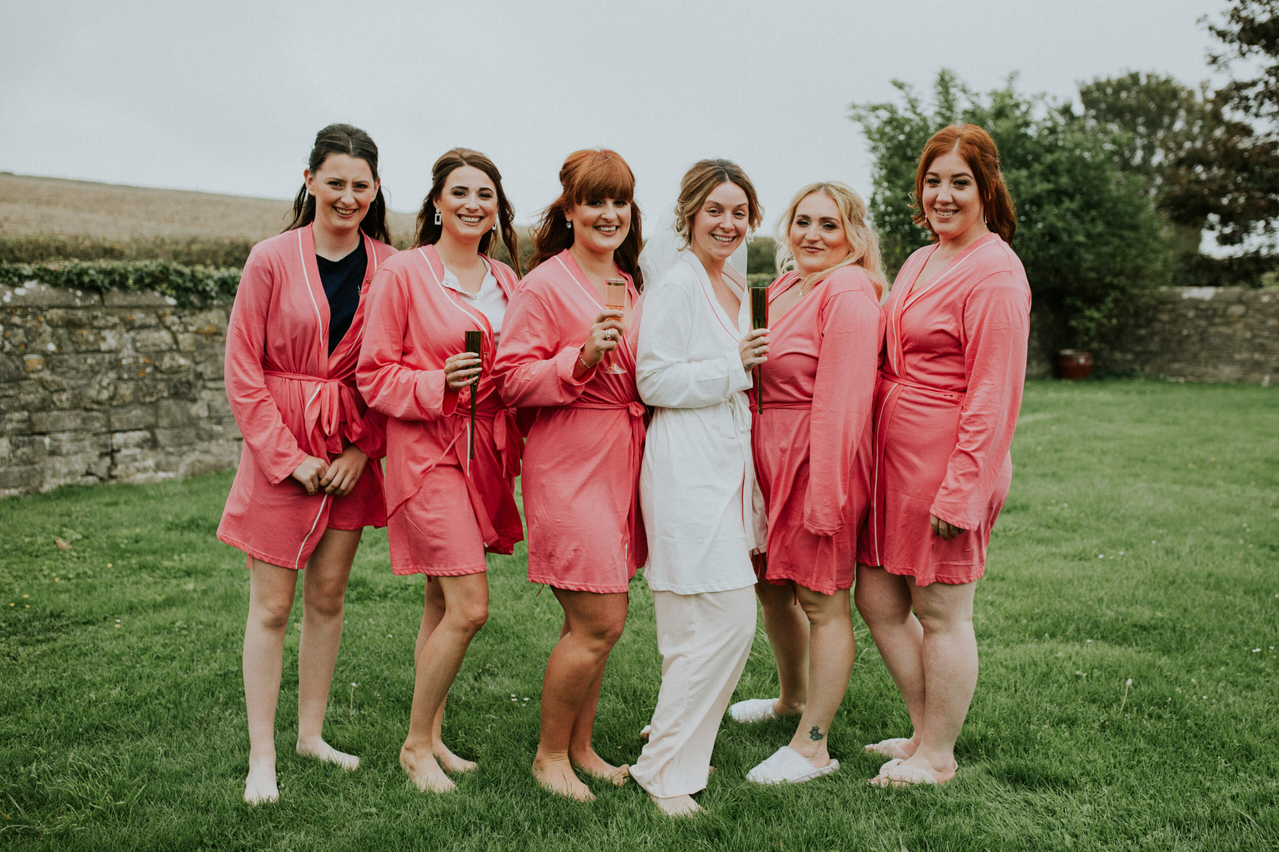 bridesmaids group shot in a field