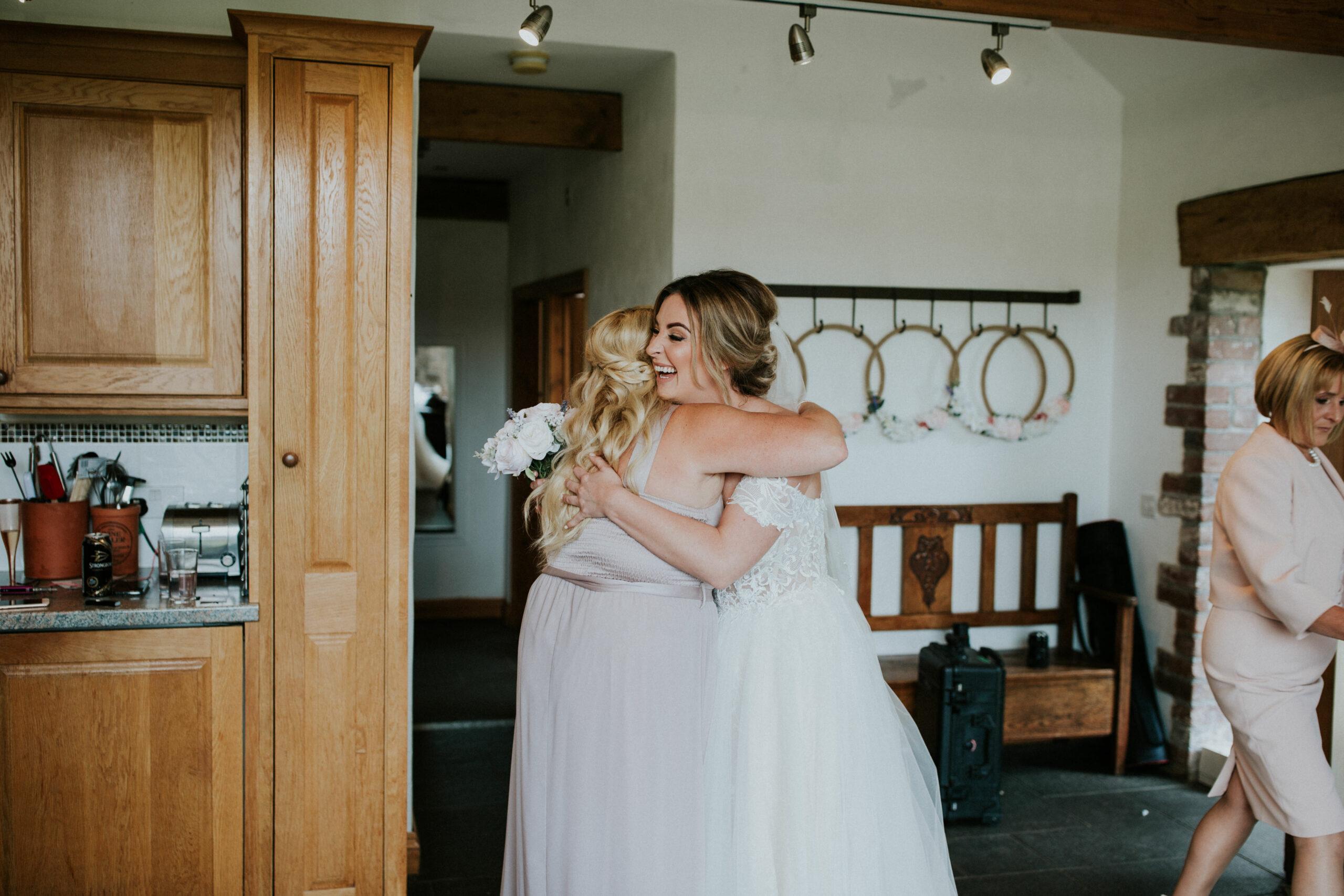 bridesmaid hugging the bride