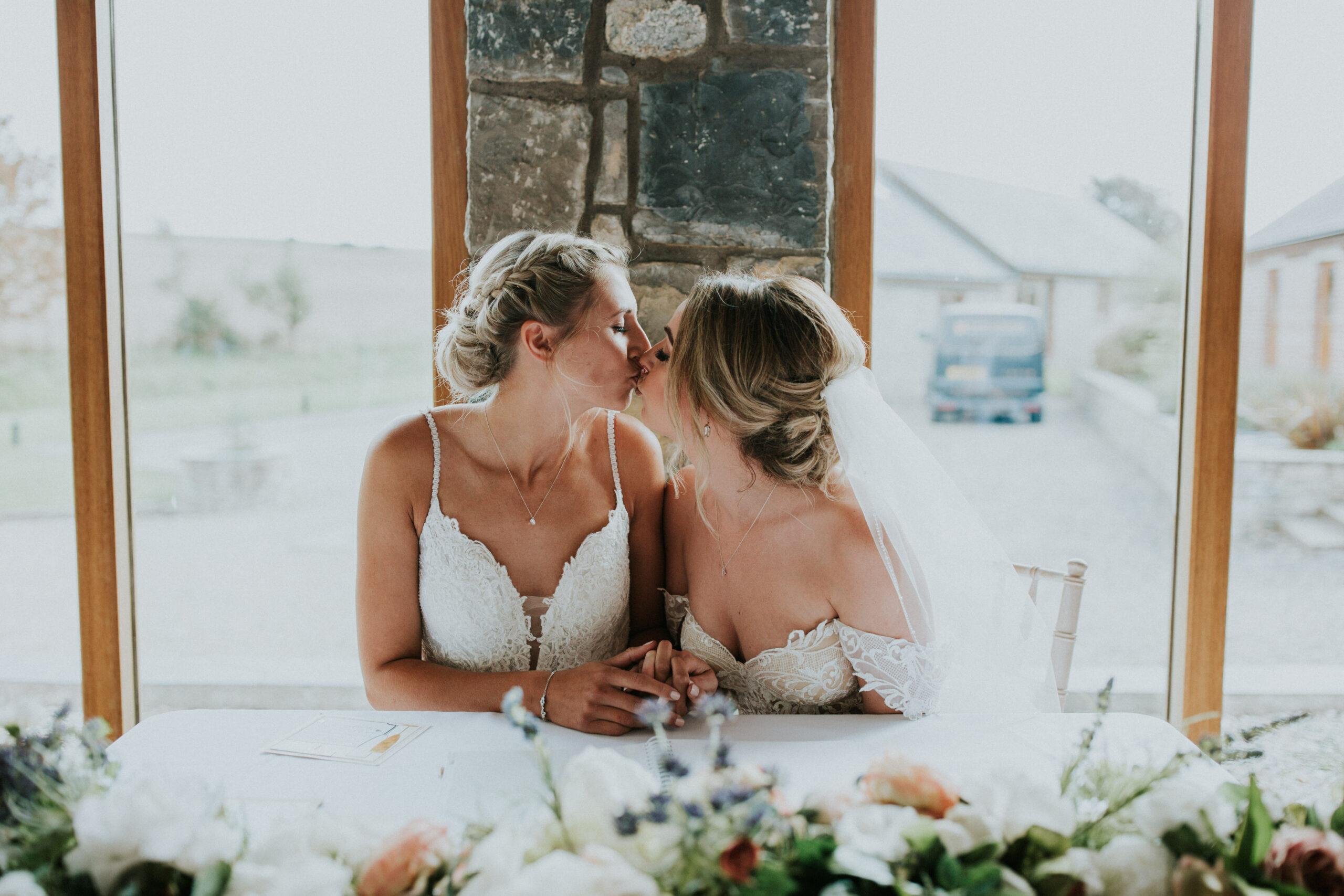 brides kissing signing the register