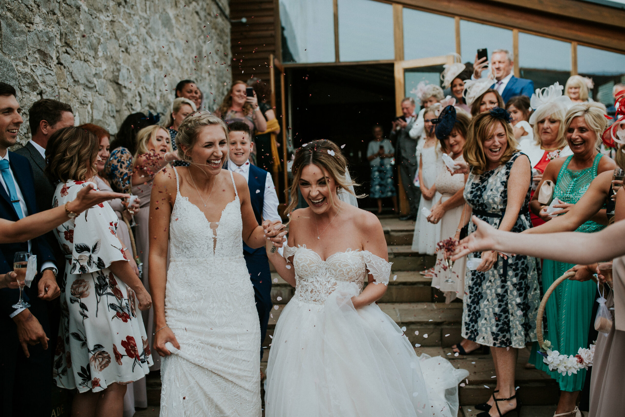 brides walking whilst guests are throwing confetti