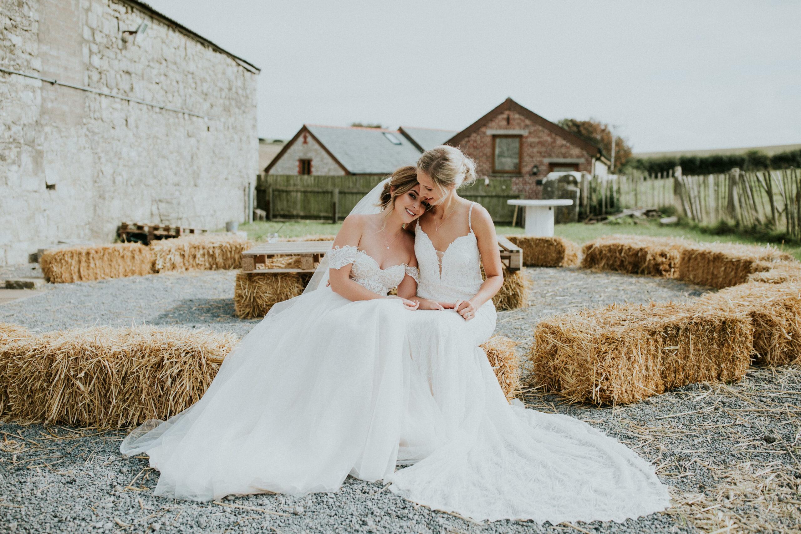 brides sitting on hay cuddling