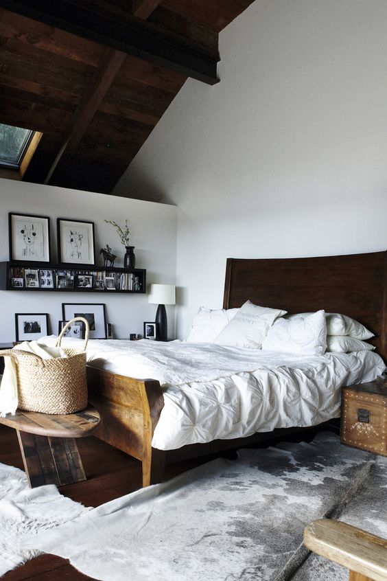 Beautiful eclectic bedroom with traditional dark wooden furniture and white paint and decoration.
