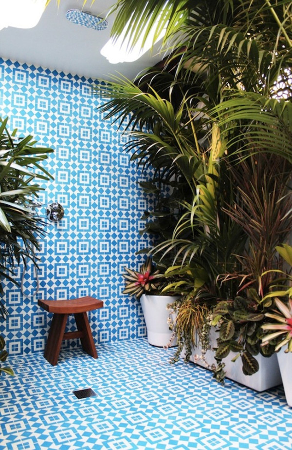 Outdoor shower covered with plants and granite flooring and wall