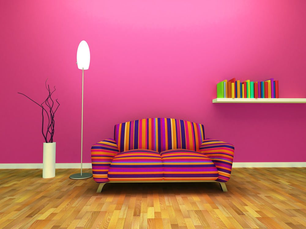 pink wall room with multi color couch