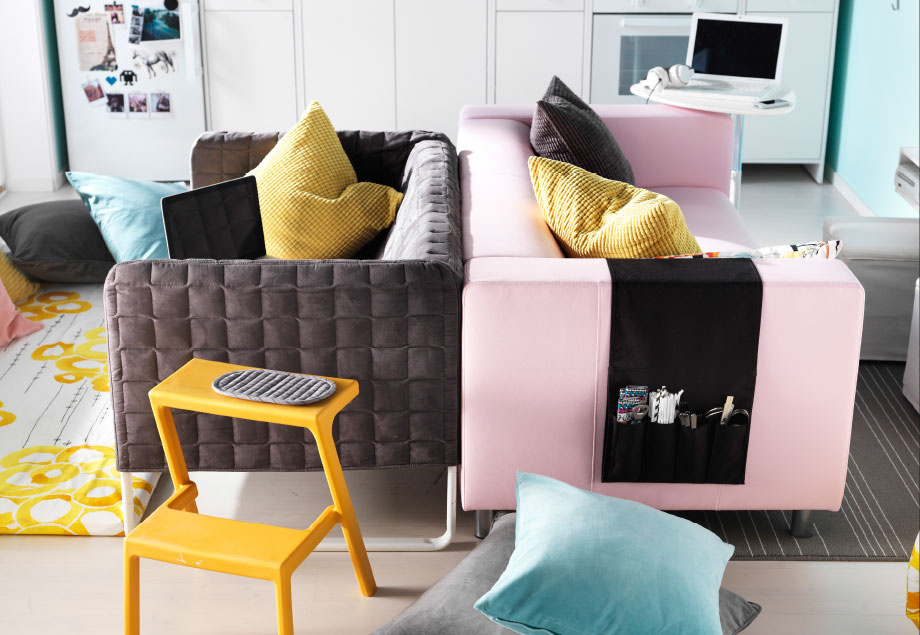 A gray and a pink sofa placed back-to-back