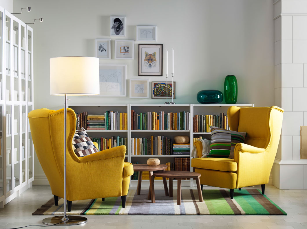 A light living room with two yellow wing chairs, nest of two tables in walnut