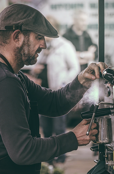 An older, male barista steaming milk in a cafe wearing a cabbie hat and a long sleeved henley.