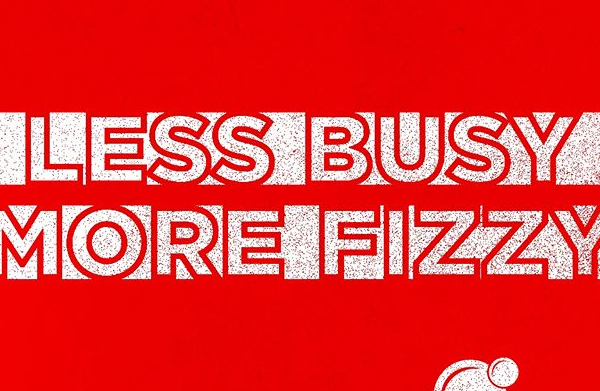 "Red Text on White Stripes on a White Background Reading, ""Less Busy More Fizzy"""