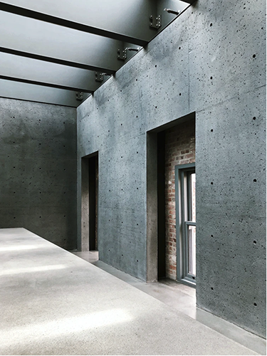 An interior photo of a sleek, modern interior with concrete floors, exposed I beams, and exposed brick.