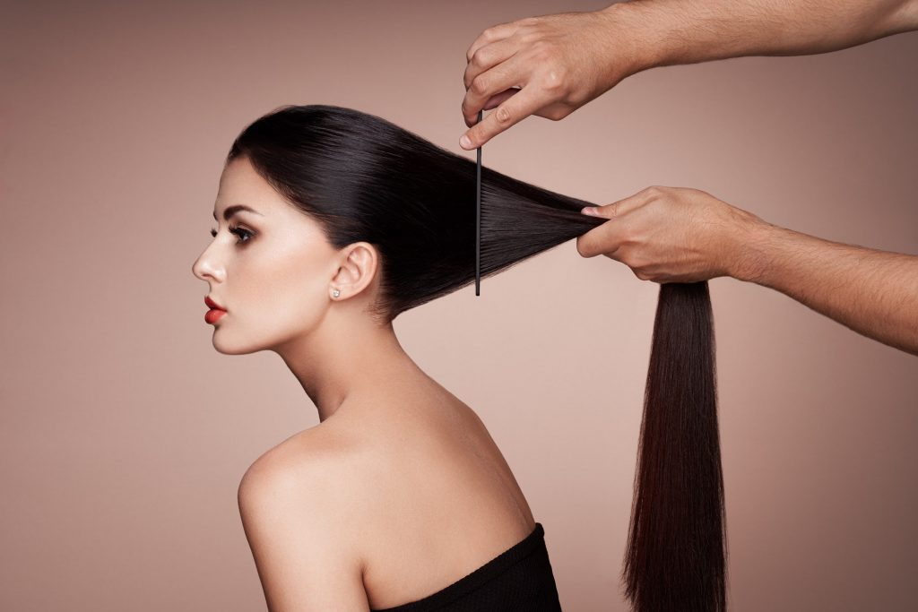 Hairdresser combs the hair of a woman