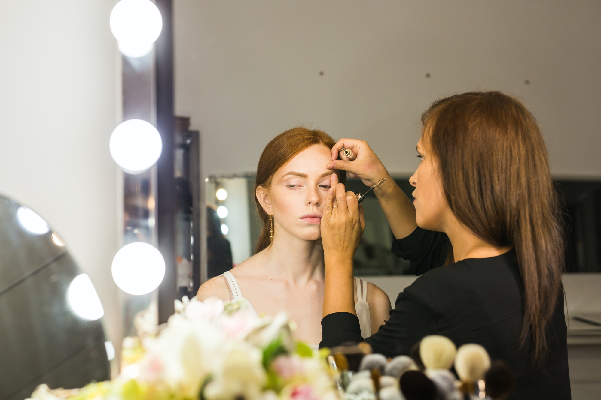 Make-up artist working with brush on model face