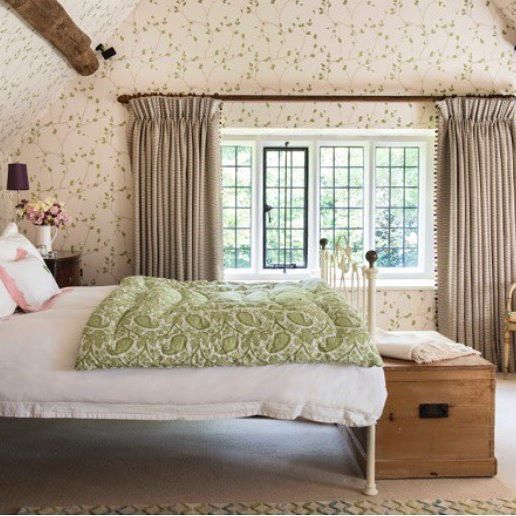 A Master bedroom in one country project by Antonia Stewart. The room was wrapped in a wallpaper that was especially coloured for this  room, taking it all the way up into the A-shaped ceiling space for the maximum effect.
