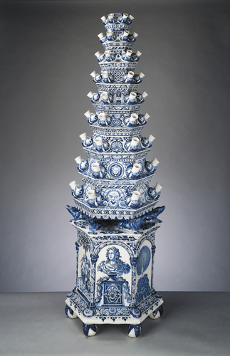 Tulip vase, Adriaen Kocks, 1694. Royal Collection Trust, UK. Many of Queen Mary II's Delftvaseswere described in the inventories of her palaces at Het Loo and Hampton Court as standing on the hearth. Flower vases such as these were used to ornament the fireplace during the spring and summer when fires were not lit. Each of the nine hexagonal stages was made separately, with a sealed water reservoir and six protruding grotesque animal mouths, into which the cut stems oftulipsor otherflowerscould be placed.