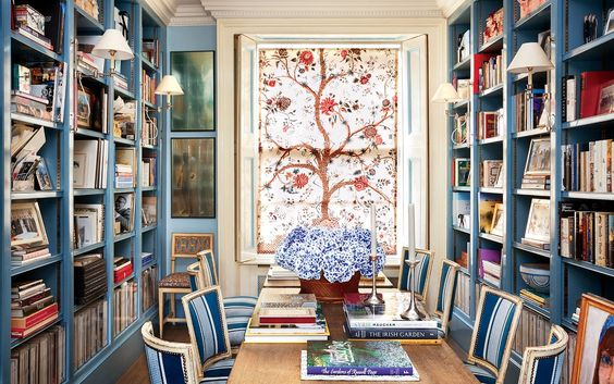 Caroline Sieber's dining-room library is crowded with the monographs that Caroline drew on for inspiration to design her London home —Jacques Grange, Elsie de Wolfe, and Madeleine Castaing among them. A panel of Braquenie's Tree of Life hangs on the window. Vogue UK. Oberto Gili photography