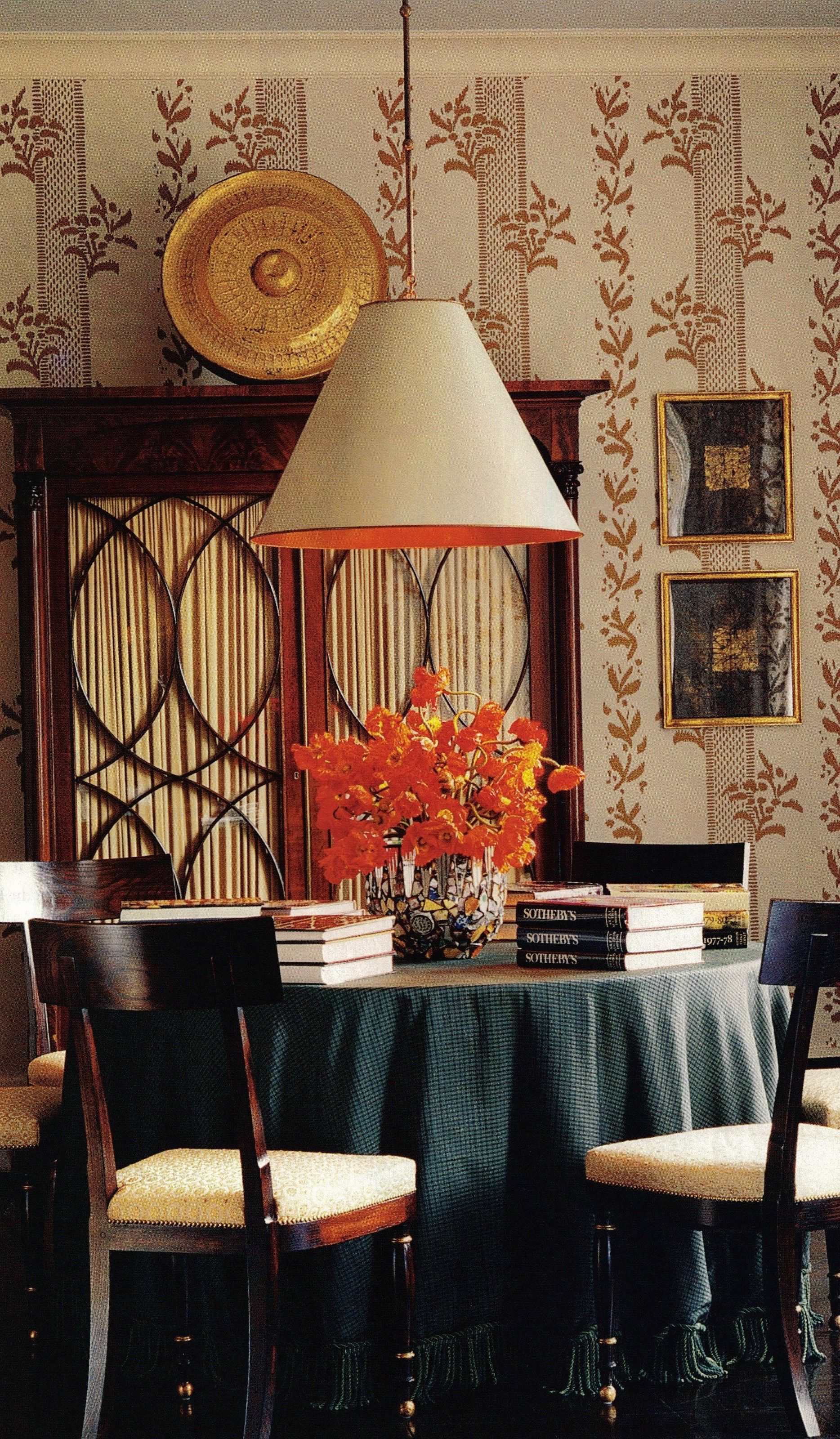 A dining room by Albert Hadley. It has a light blue ceiling, a favourite Hadley hue for the upper plane. The American Empire mahogany armoire is topped by a Tibetan gong. Next to them are two works on paper by Connecticut artist Mark Sciarillo, also a metalworker, who made the sculpted bronze base of the living room's coffee table. The vellum lampshade, the Eyelet gold-on-ivory wallpaper, and the chairs are all Hadley's designs. Fernando Bengoechega photography. House Beautiful