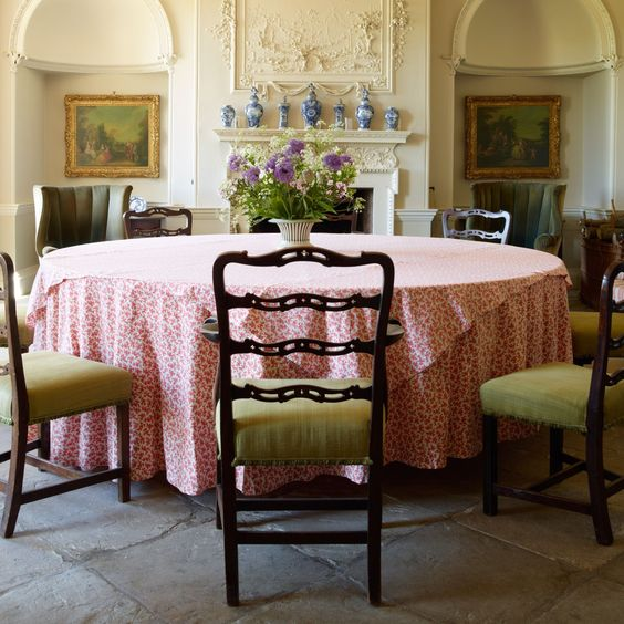 At Gateley Hall in Norfolk, owner Vivien Greenock has used her expertise as an interior designer to restore the once neglected eighteenth-century house and decorate it in a quintessential English style. In the entrance hall, which doubles as a dining room, eighteenth-century chairs surround a large circular table and a collection of Delftware is framed by the plasterwork above the chimneypiece. From the July 2014 issue of House & Garden.