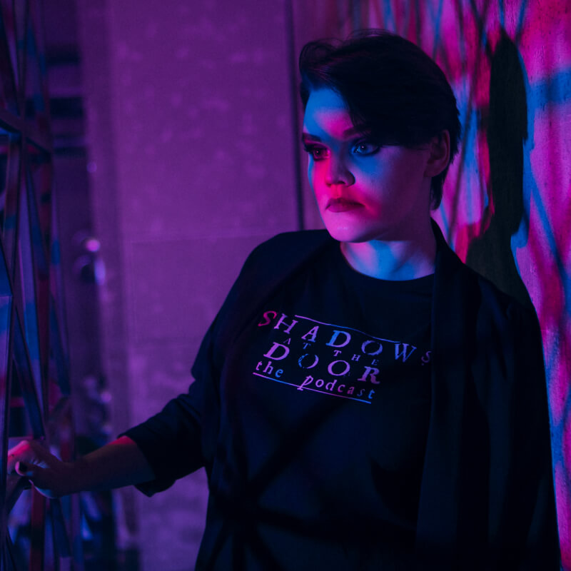 model wearing shadows at the door the podcast t-shirt in black