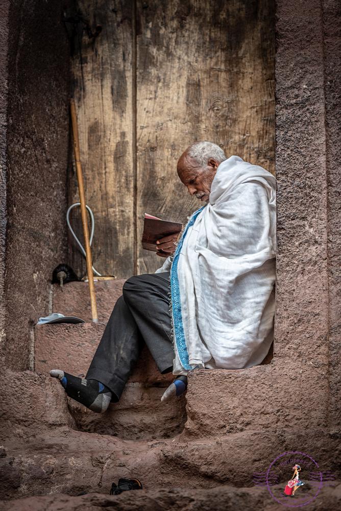 Pilgrim meditating in prayer in a nook at Bet Medhane Alem