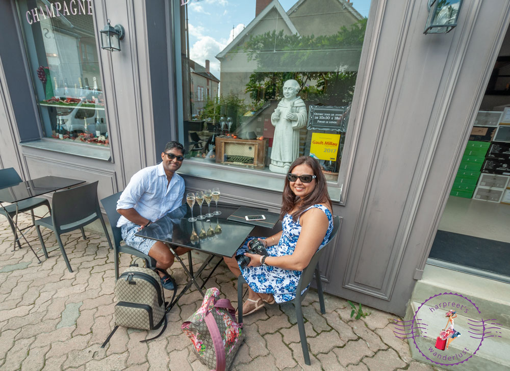 Harpreet and Wanderlustmate M at Au 36, with a statue of Dom Perignon in the window