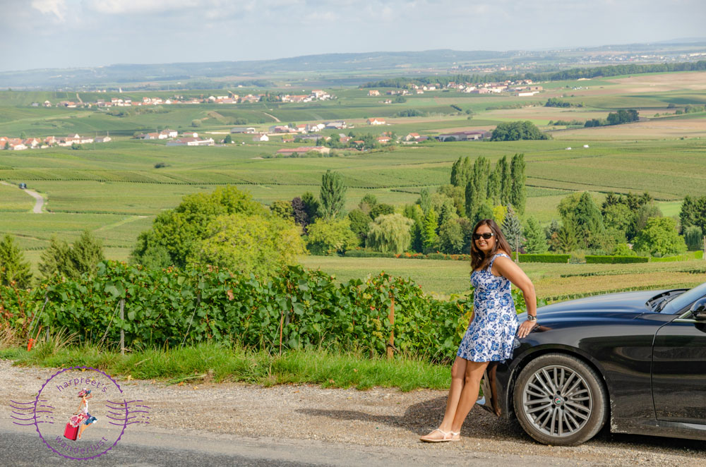 Harpreet in a blue dress leaning on a car in the vineyards
