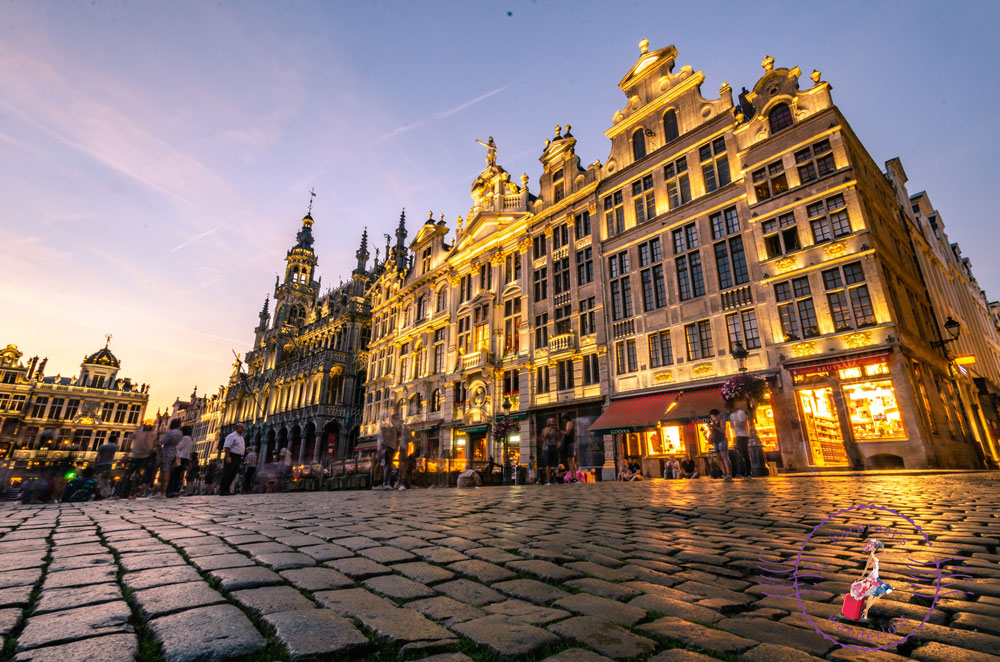 A picture of the Grand Place Brussels all lit up at night, showing the world's first Godiva store