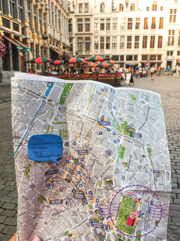 Harpreet holding a map in the middle of Grand Place Brussels for the self guided chocolate tour