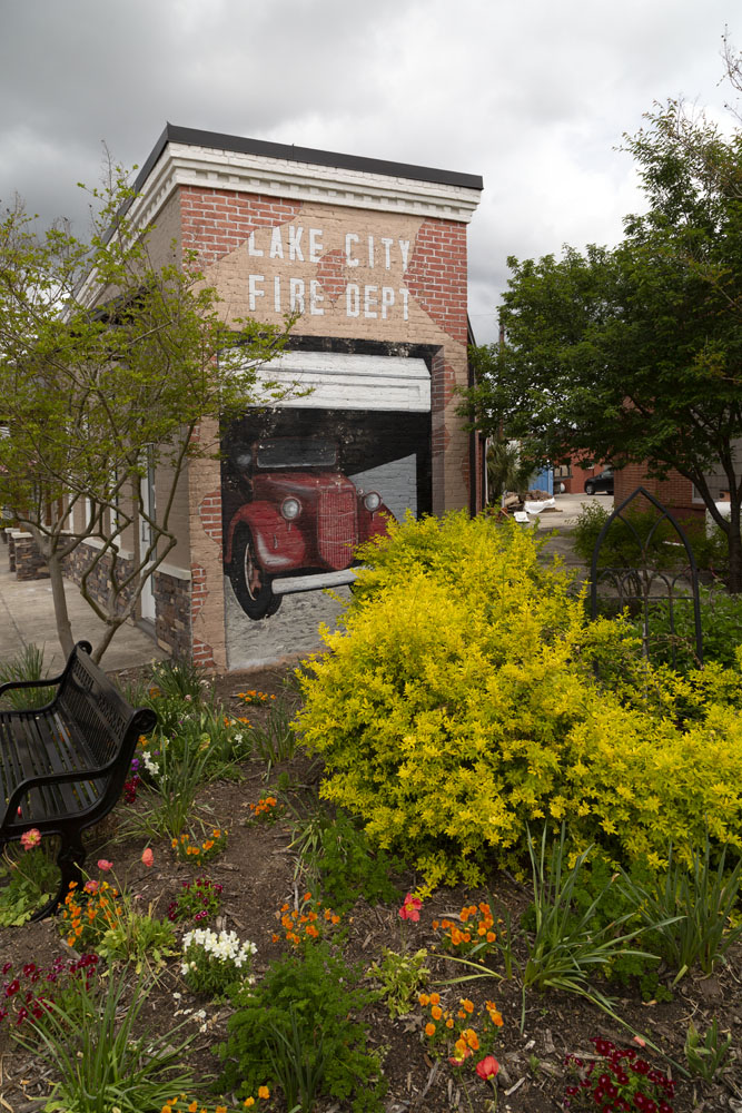Mural depicting the Lake City Fire Department by shrubs and flowers.