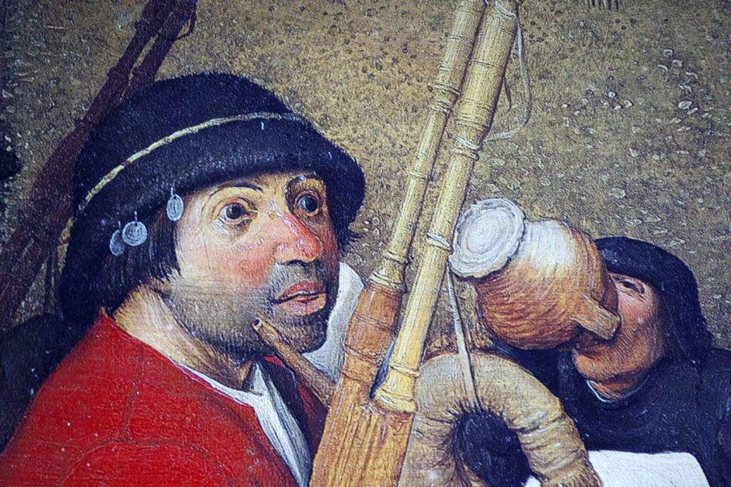 Detail of a male peasant character with bagpipes in a painting by Pieter Bruegel the Elder