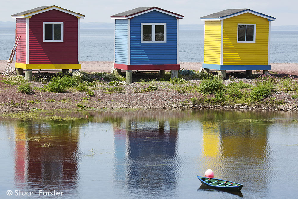 Colourfully painted huts by the shore of the Atlantic Ocean at Heart's Delight-Islington in Newfoundland and Labrador, Canada.